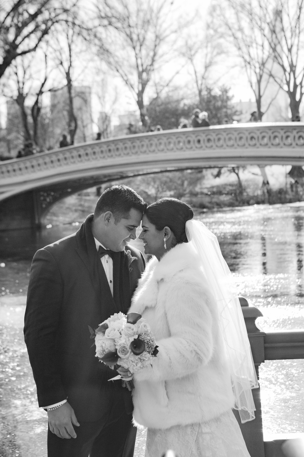 Black and white portrait of bride and groom under bridge