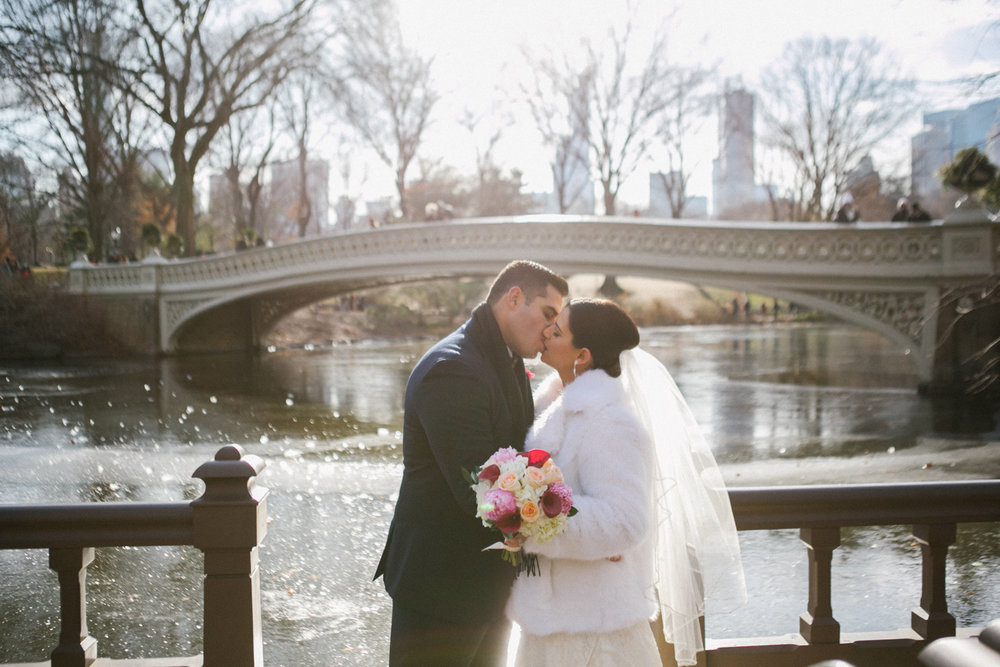 Bride and groom kiss under the bridge