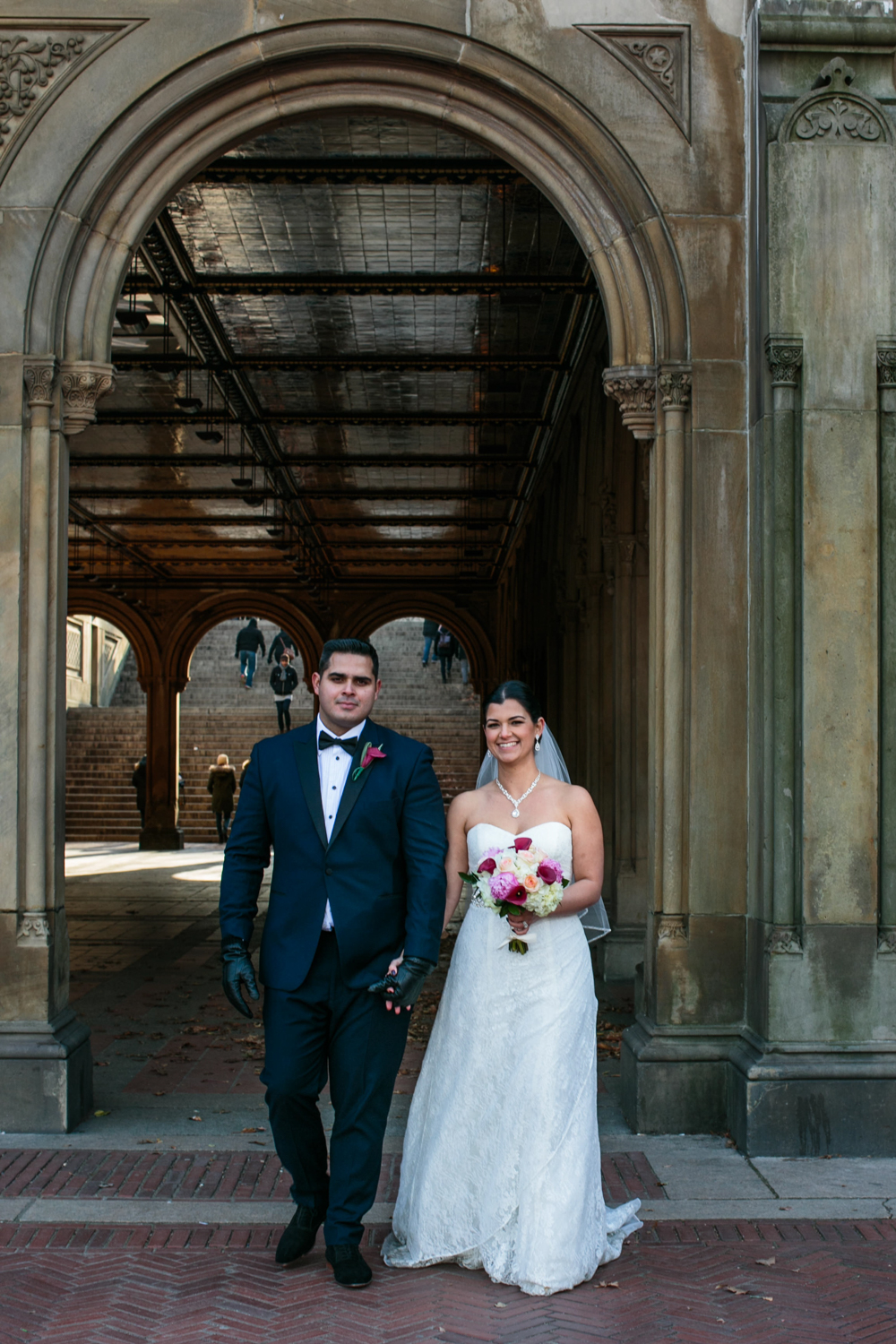 Newlyweds under beautiful arches in NYC