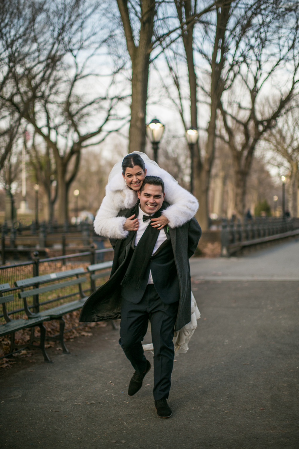 Groom gives bride a piggy back ride in NYC