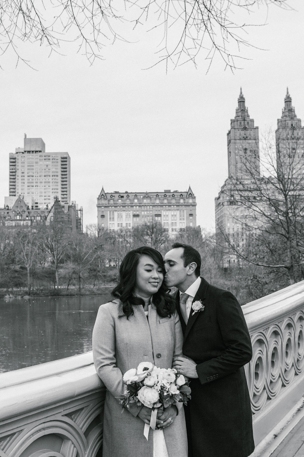 black and white portrait of groom kissing his bride