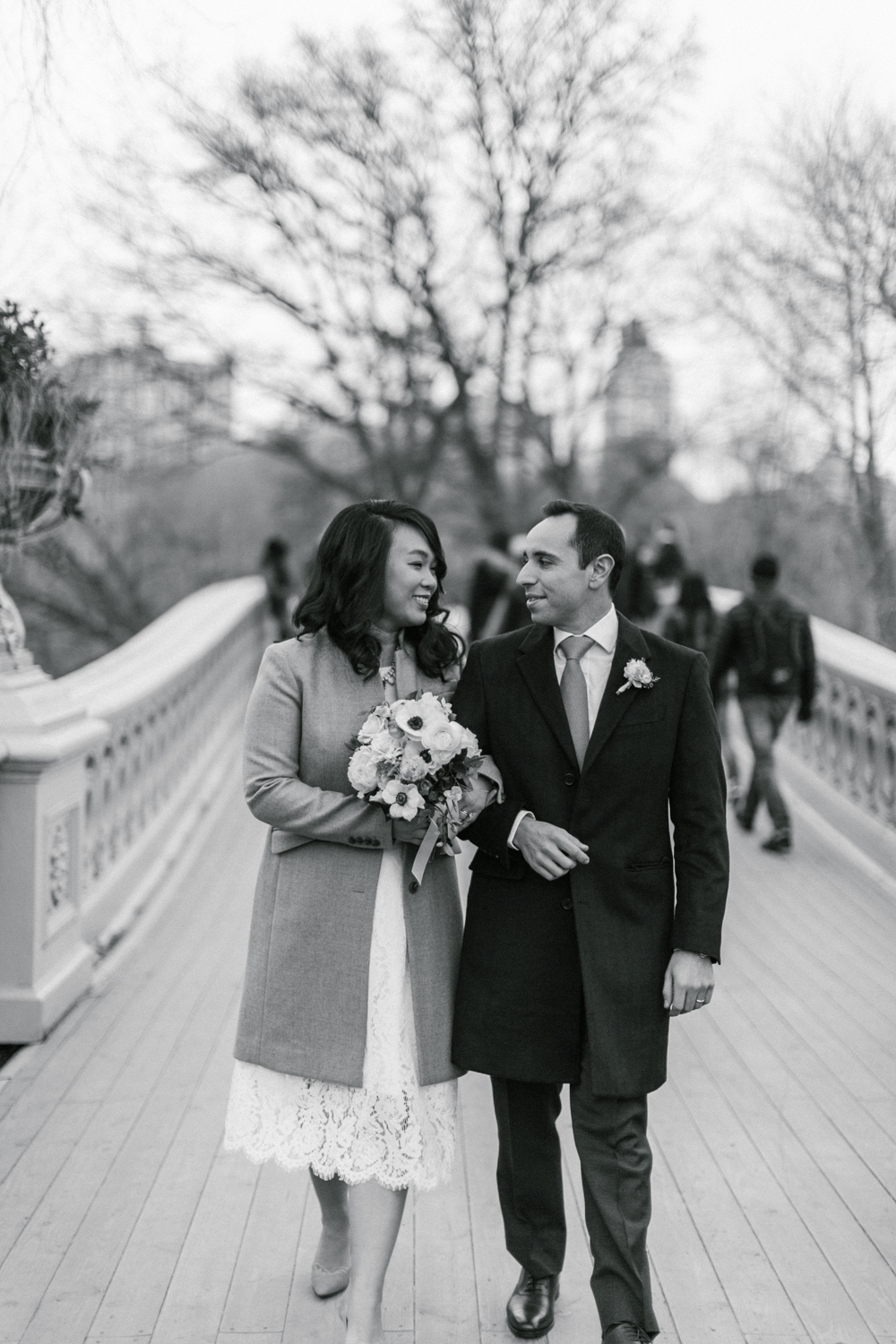 Black and white portrait of newlyweds walking together