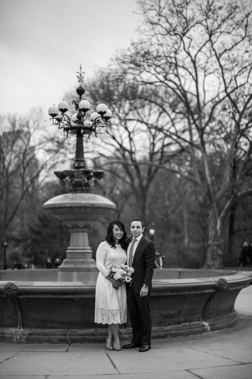 Black and white portrait of bride and groom by fountain