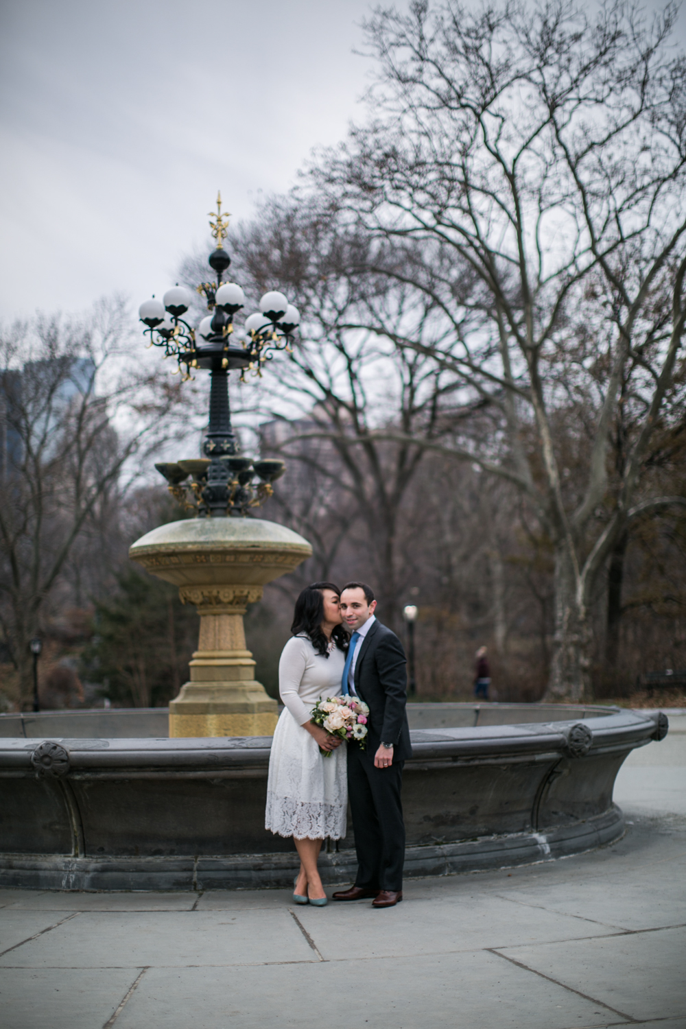 bride kissing groom in front of fountain