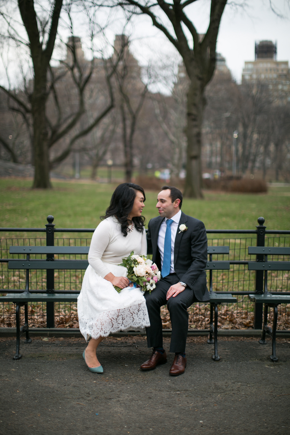 Bride and groom on park bench in NYC