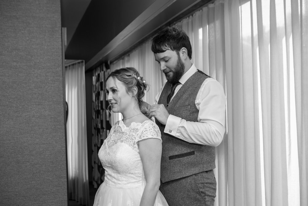 NYC groom helps his bride put on her necklace before elopement ceremony.