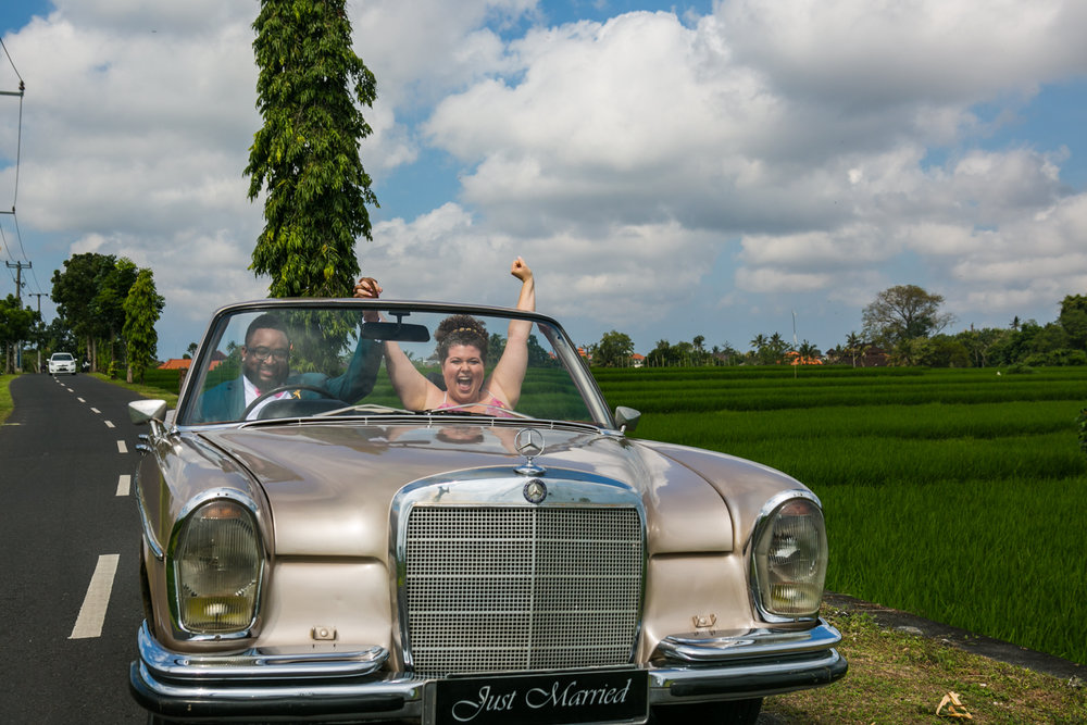 photograph of Bride and groom in classic car