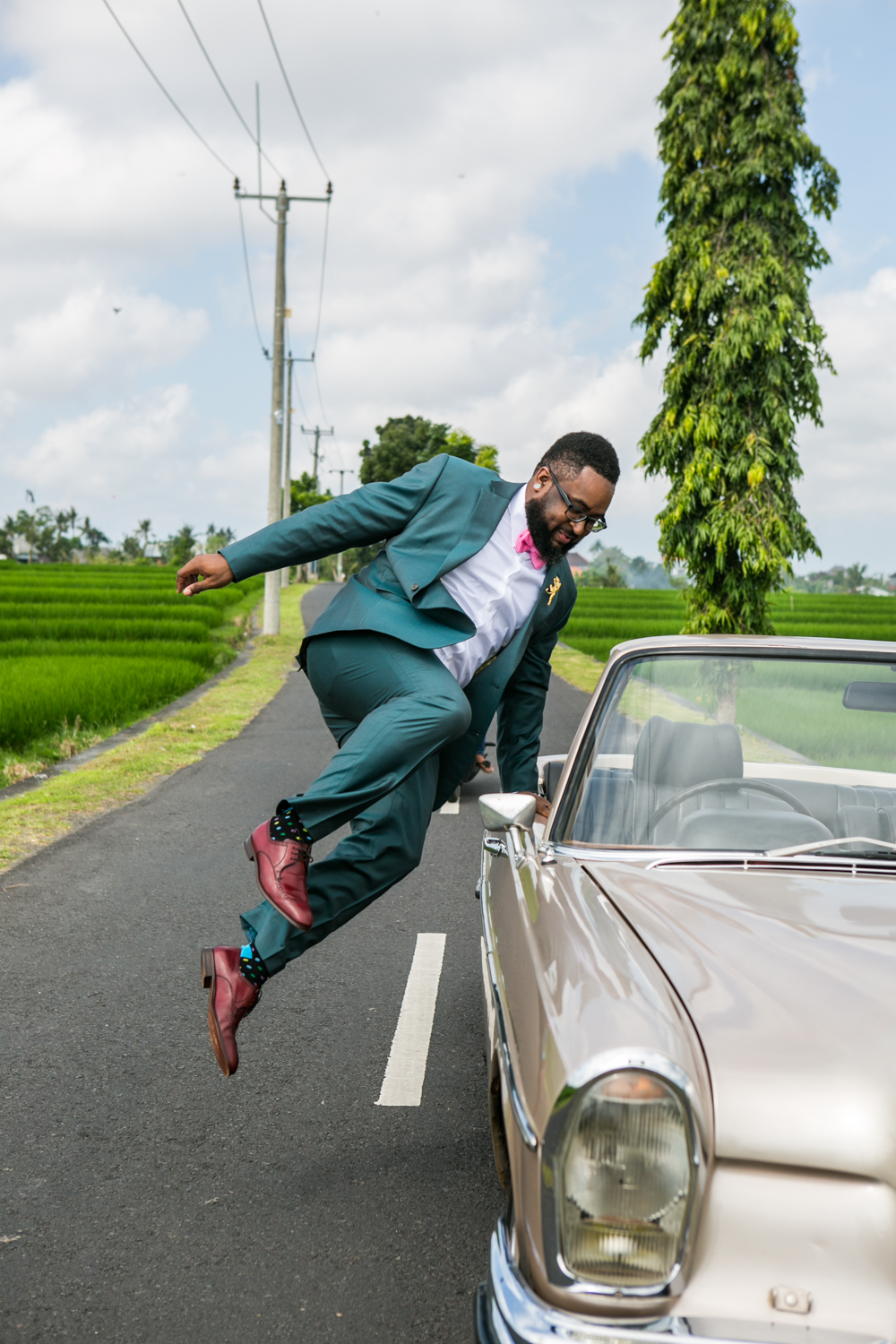 Groom hopping into classic car in Bali