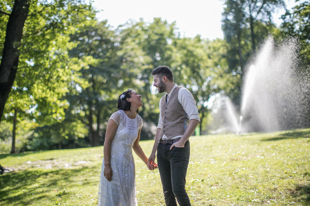 Bride and Groom laughing in front of sprinklers in Central Park.