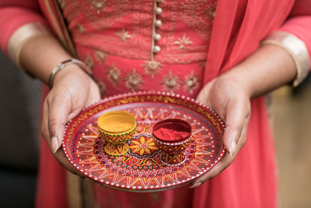 Turmeric and Vermillion powders offered to ladies at an Indian wedding reception.