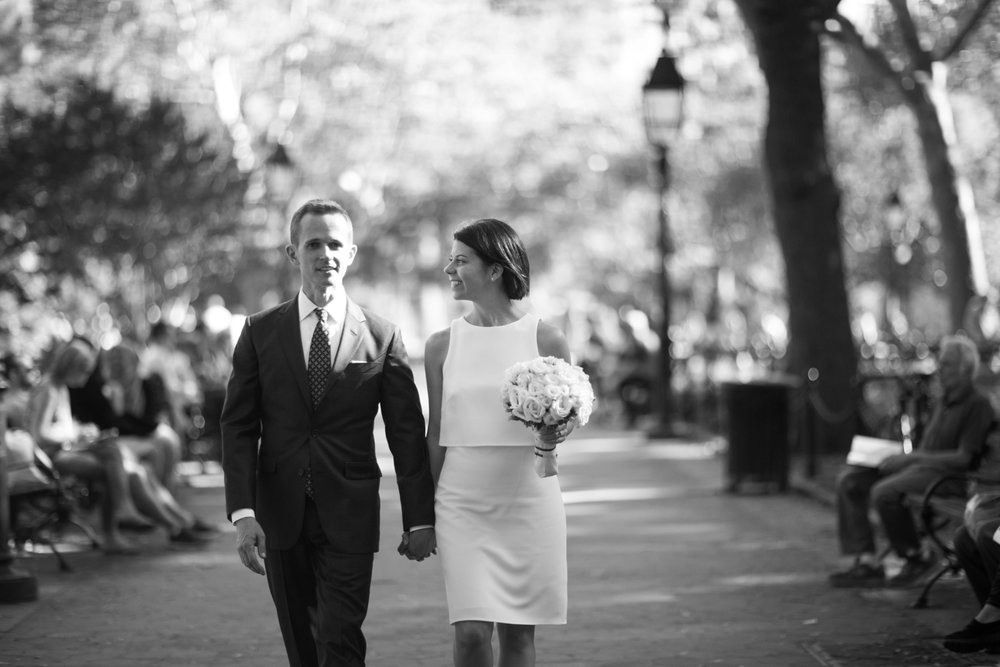 Black and white portrait of bride and groom walking through the park hand in hand.