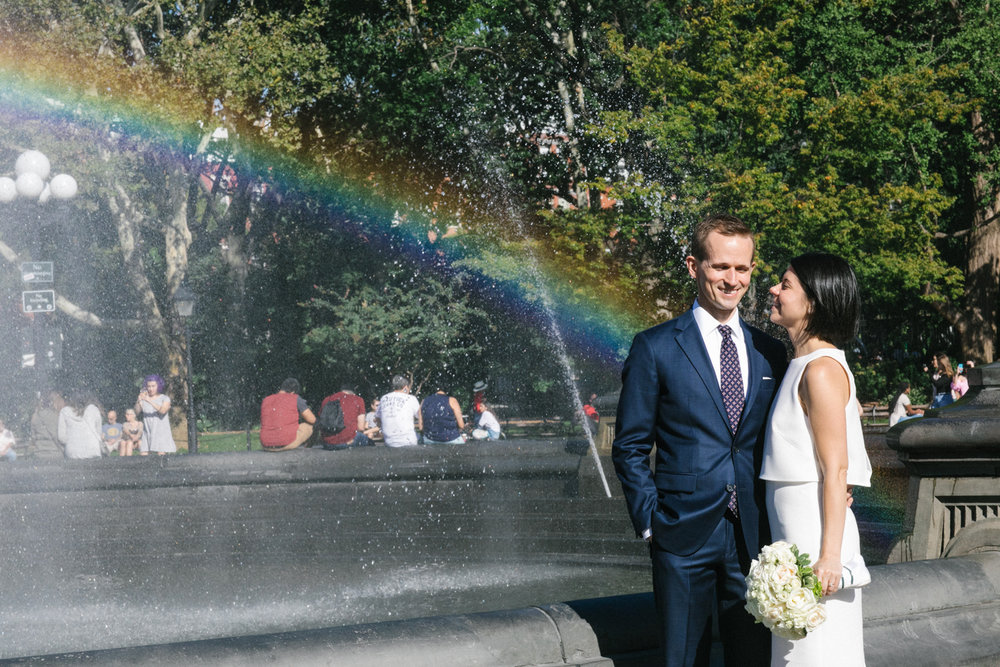 Bride and groom pose in front of a rainbow.