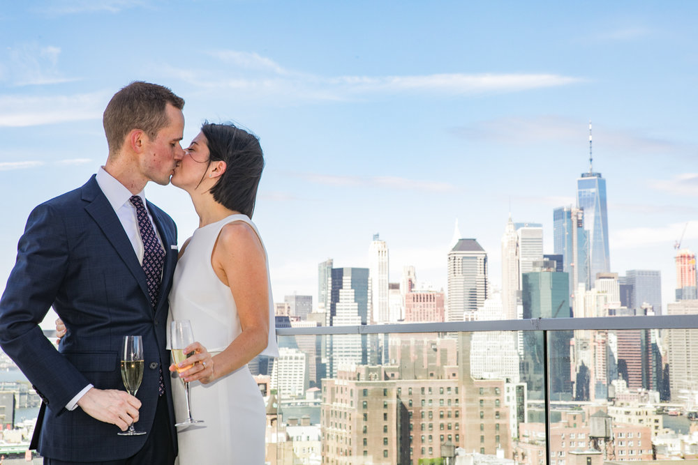 Bride and groom kiss in front of the New York City Skyline.