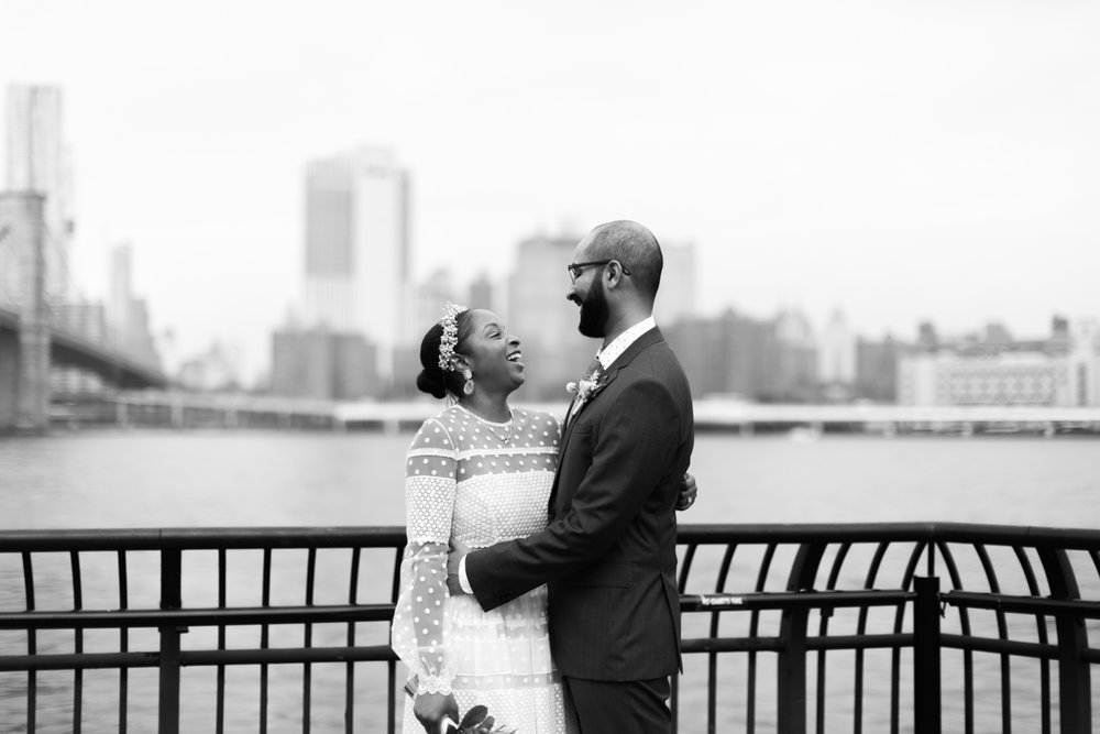 Black and white photo of bride and groom laughing in Brooklyn Bridge Park.