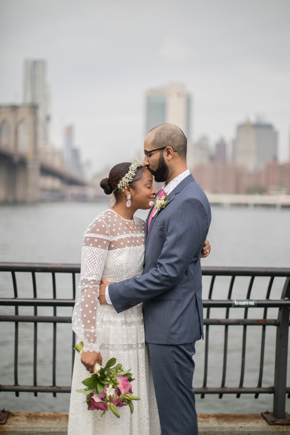 Bride and groom embrace after their wedding ceremony in Brooklyn Bridge Park.