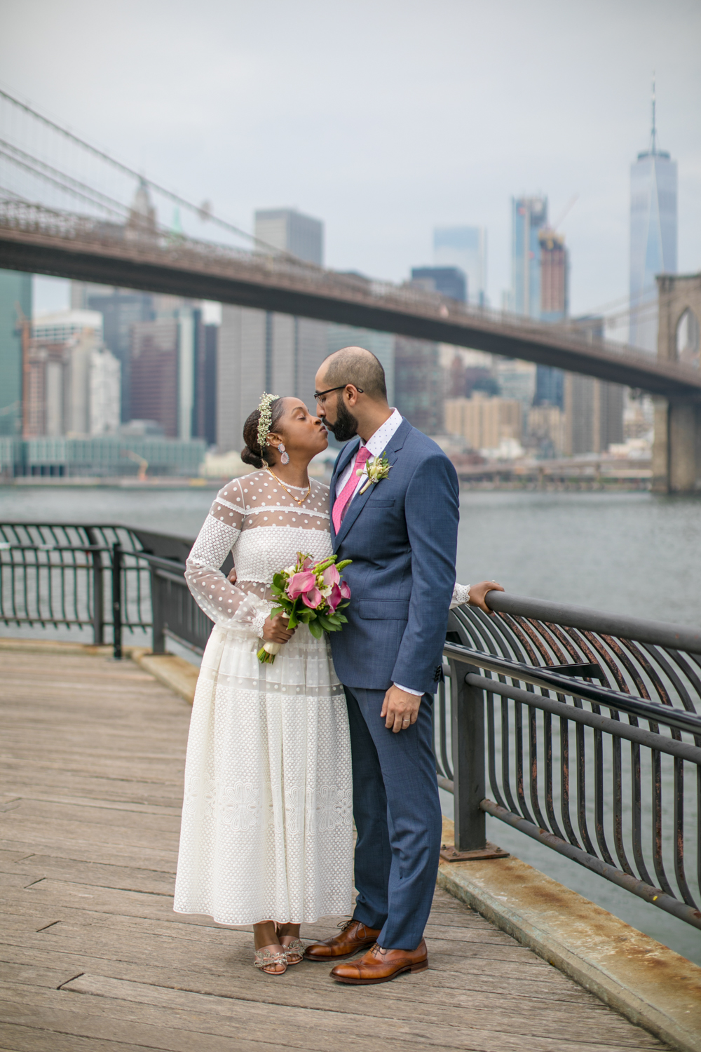 A bride and groom kiss after their  Brooklyn Bridge Park Wedding Ceremony.