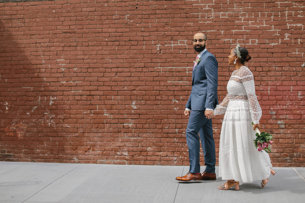 A bride and groom take a walk in front of a brick wall.