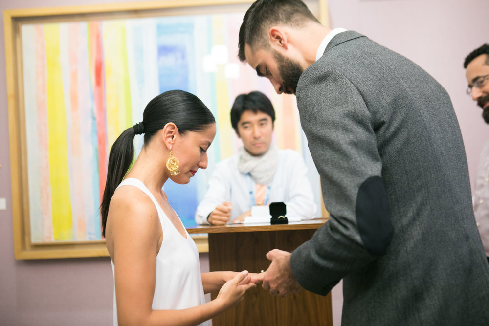 Bride and groom exchange rings at their City Hall wedding in New York.