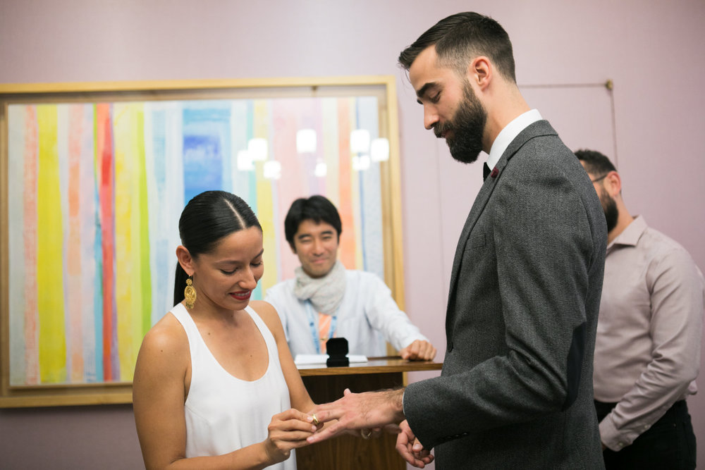 Bride and groom exchange rings in an intimate City Hall wedding in New York.