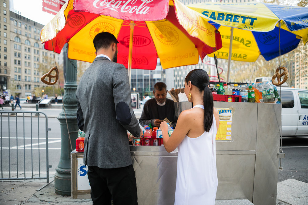 Bride and groom stop at a hot dog stand in New York on their wedding day.