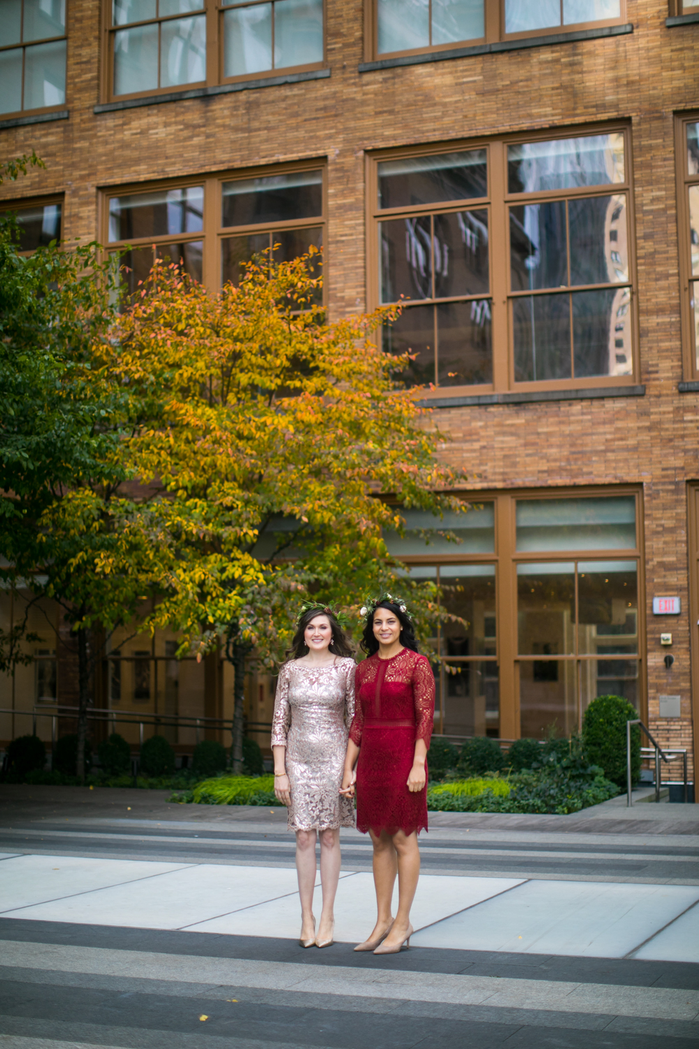 Portrait of brides holding hands on the sidewalk.