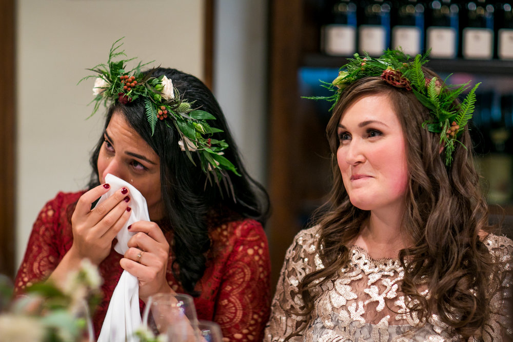 A bride cries while her father gives a wedding toast.