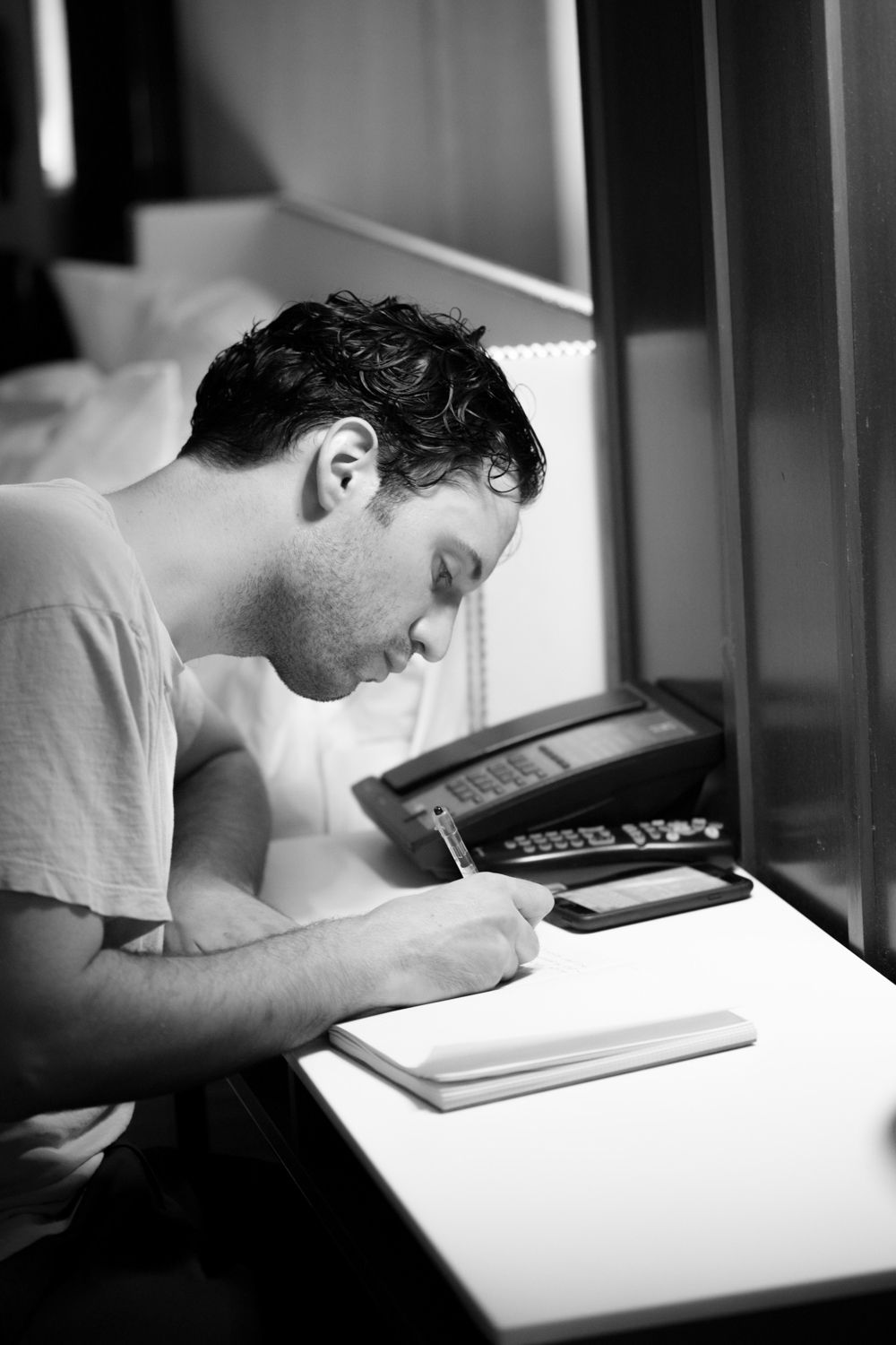 Photo of the groom writing in a journal on the morning of his wedding.