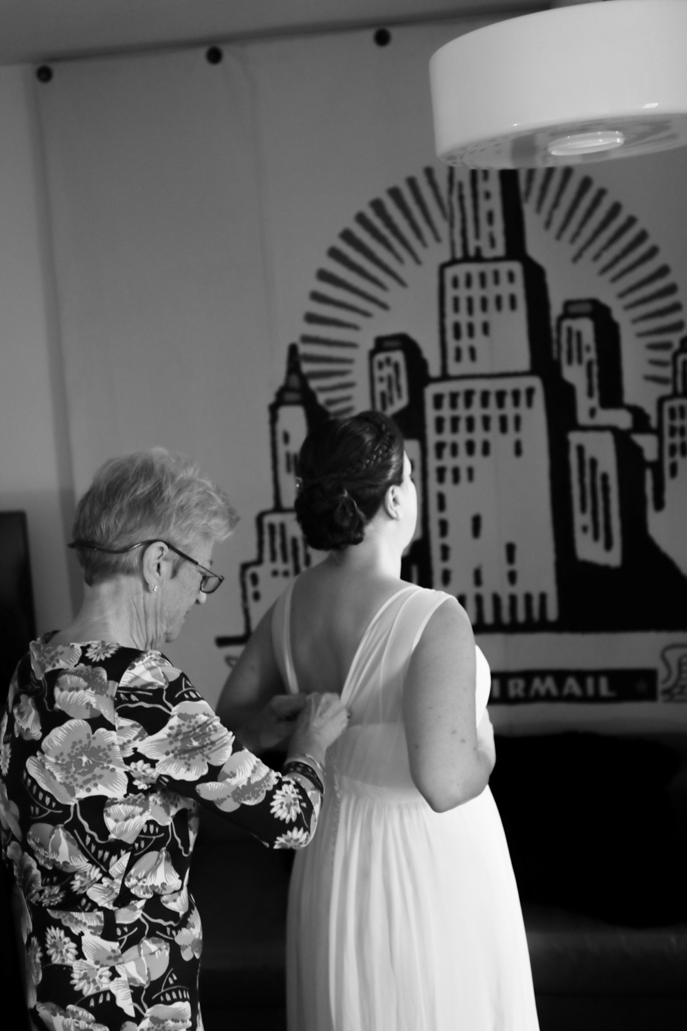 Bride putting on her ong white wedding dress from the Jenny Yoo collection at Modcloth hangs in the ACE Hotel in New York City.