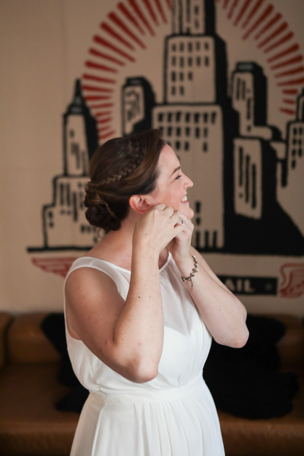 Bride puts on earrings before her wedding at the ACE Hotel in New York City.