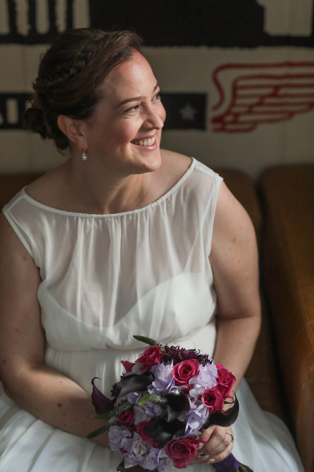 Portrait of a bride with her pink and purple bouquet.