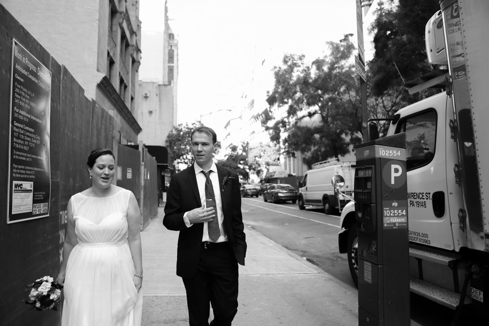 Black and white portrait of a bride and groom walking together in New York City.