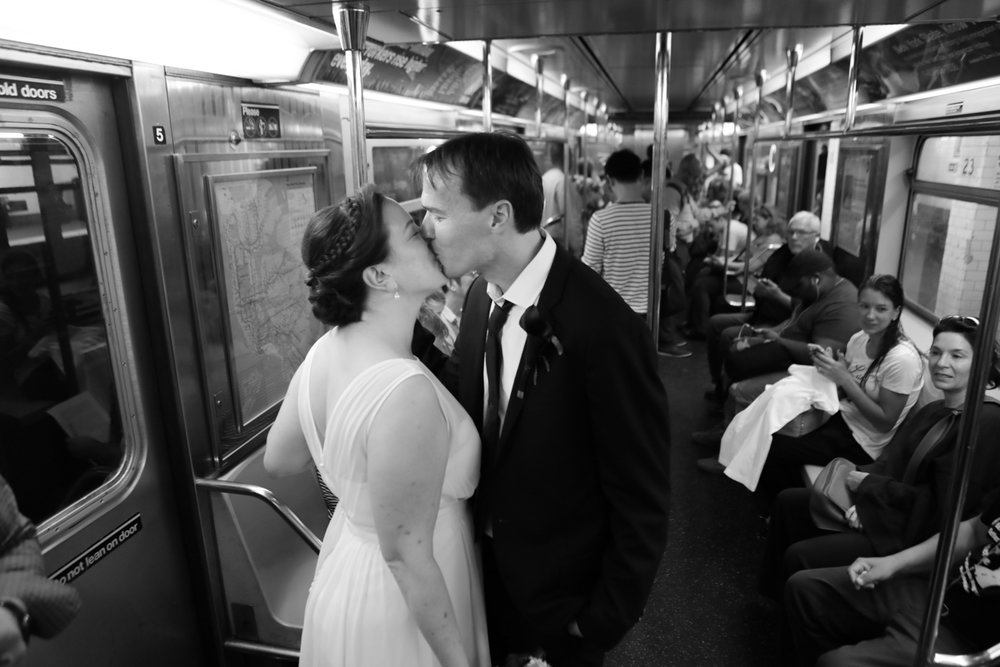 Bride and groom kiss on the subway on the way to their City Hall wedding in New York City.