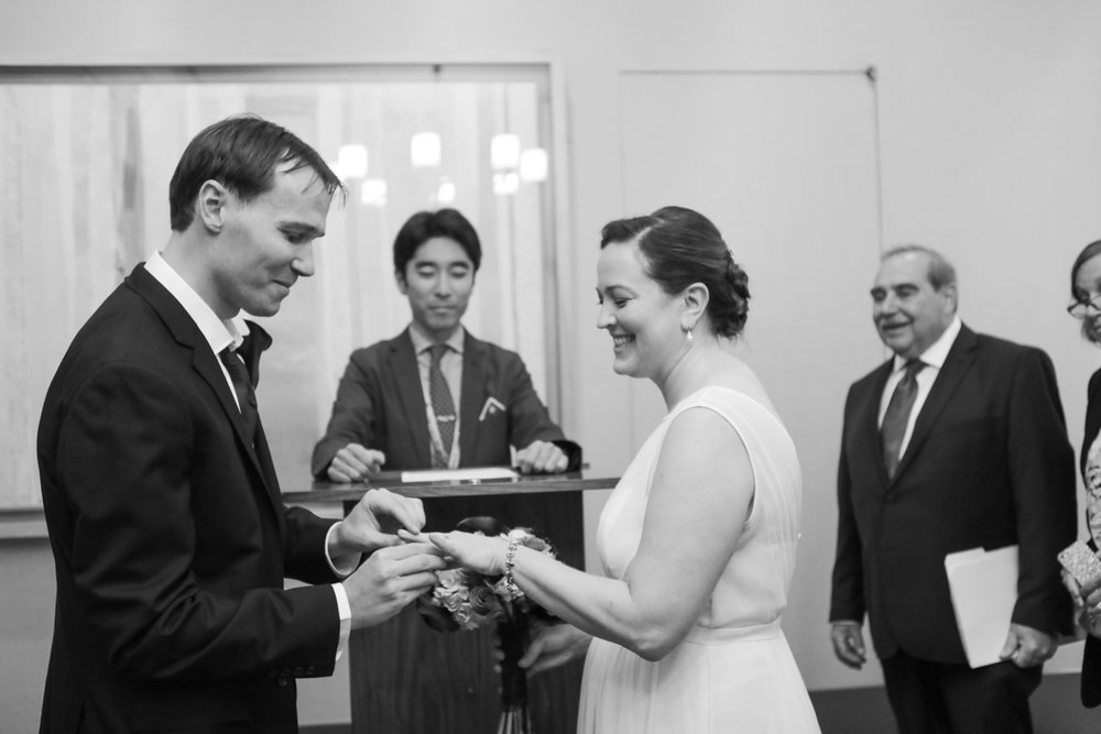 Black and white wedding photo of the bride and groom exchanging rings at City Hall.