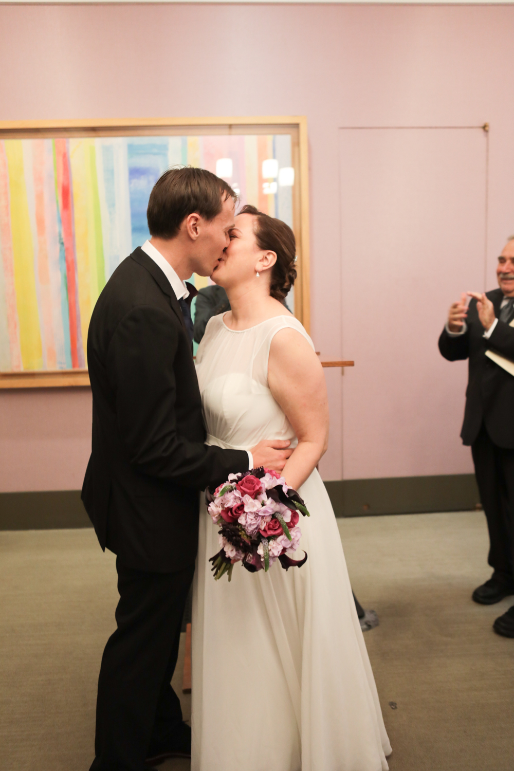 Portrait of a bride and groom's first kiss at their City Hall wedding ceremony in New York City.