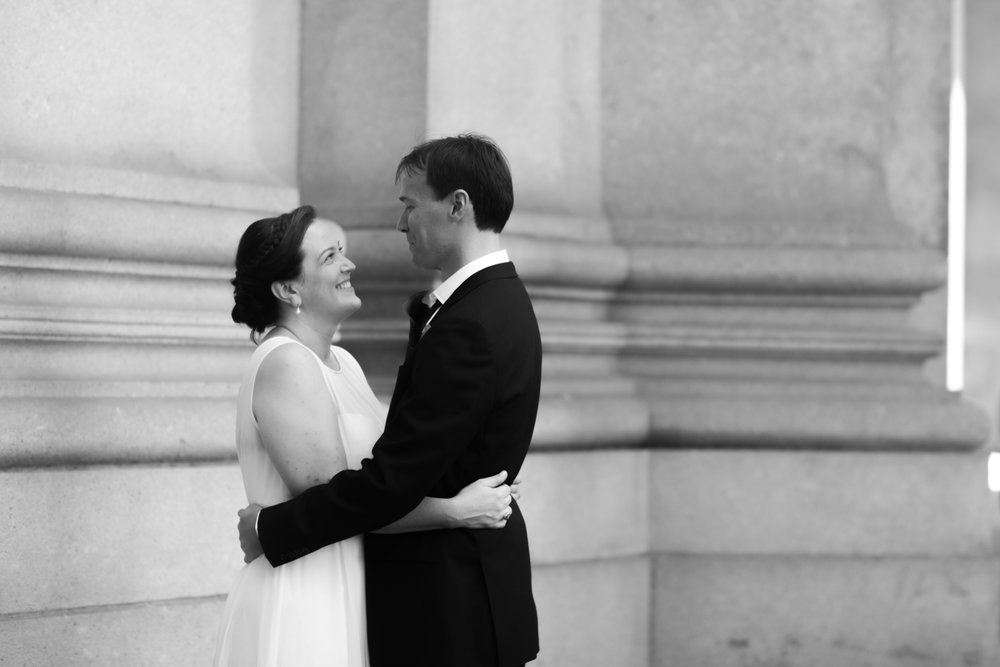 Black and white portrait of a couple embracing on their wedding day.