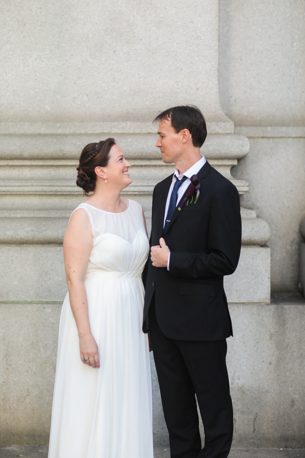 Portrait of a couple on their wedding day. The bride is wearing a Jenny Yoo Collection dress from ModCloth and the groom is wearing a dark suit and blue tie.