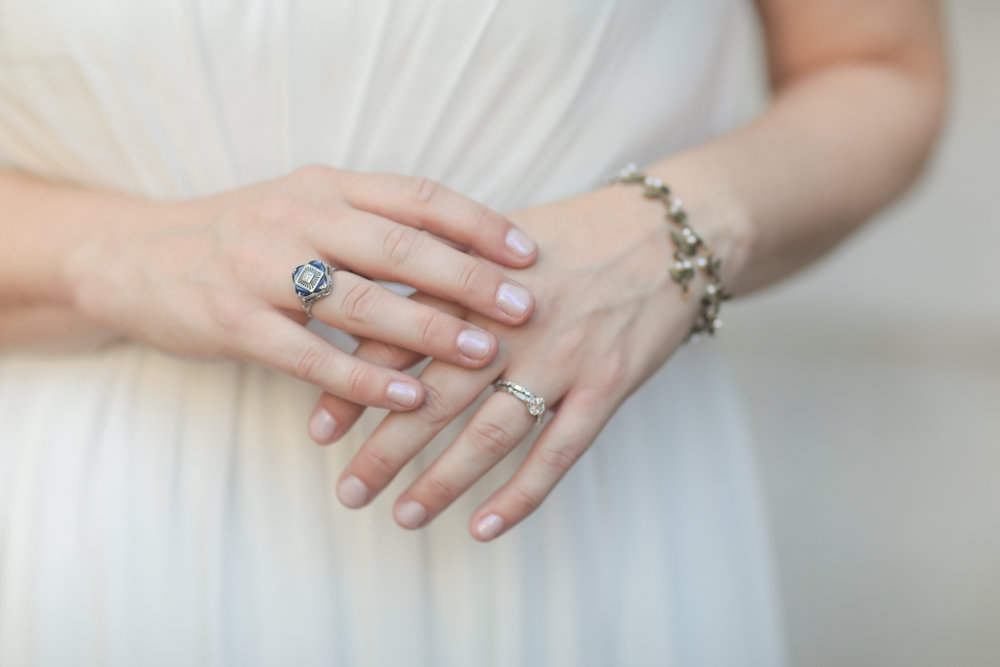 Close up of a bride's hands showing her wedding and engagement rings and her grandmother's wedding ring.