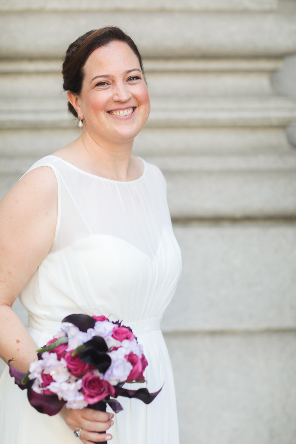 Portrait of a bride carrying a pink and purple flower bouquet.
