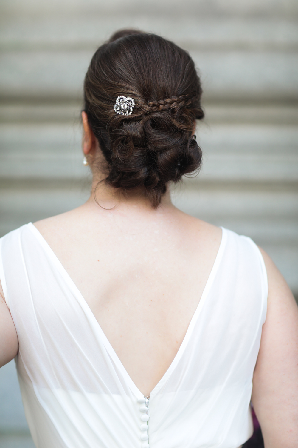 Portrait of the back of a bride's dress and homemade wedding hair clip.