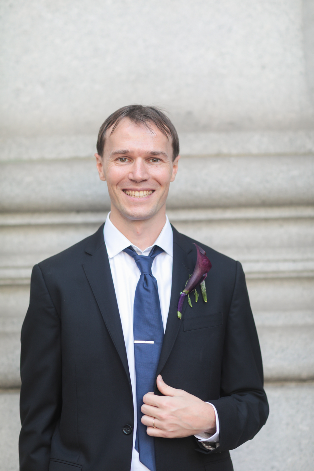 Portrait of the groom wearing a dark suit, navy blue tie, and purple boutenniere.