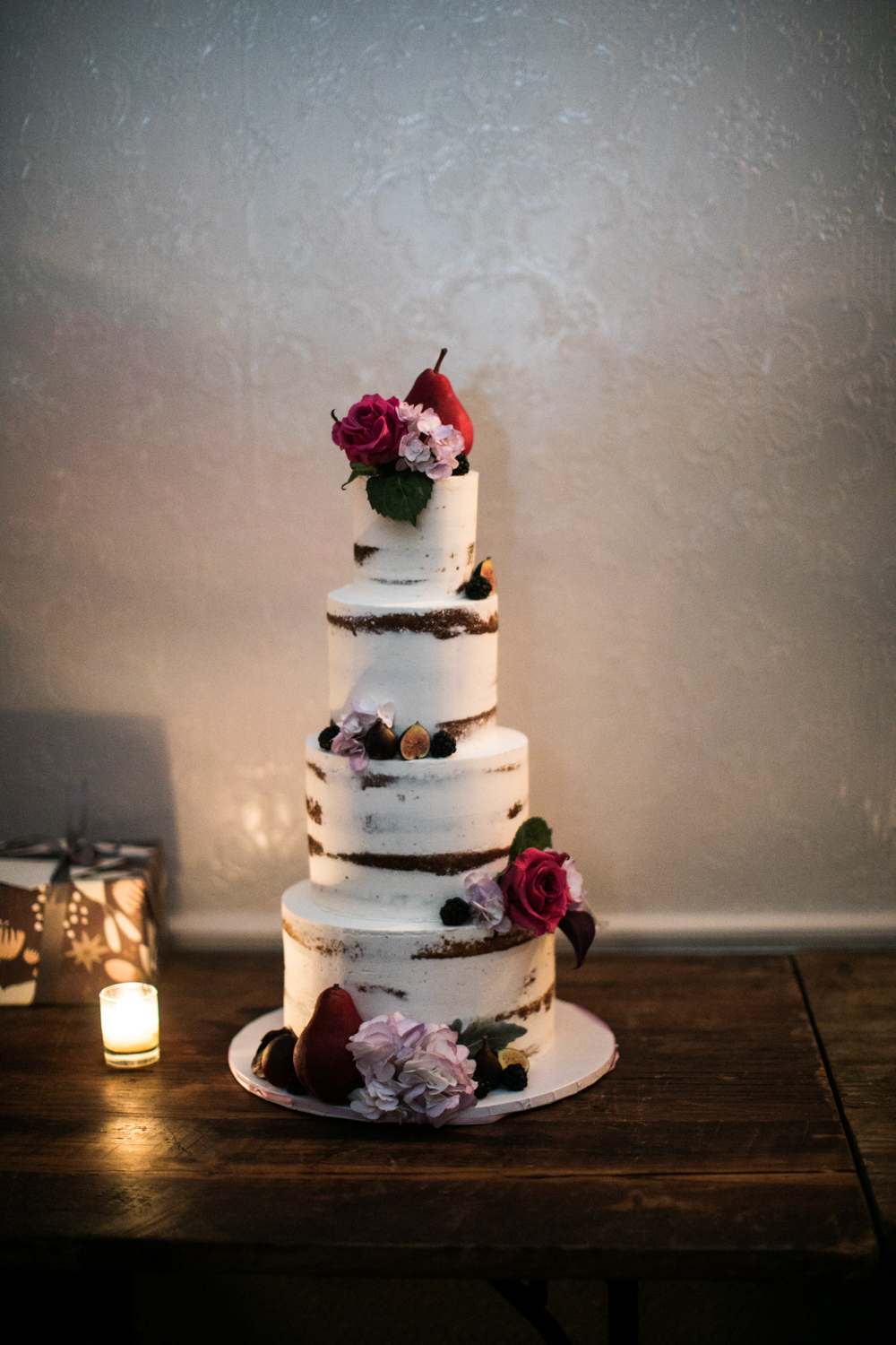 Four-tier wedding cake decorated with flowers and fruit.