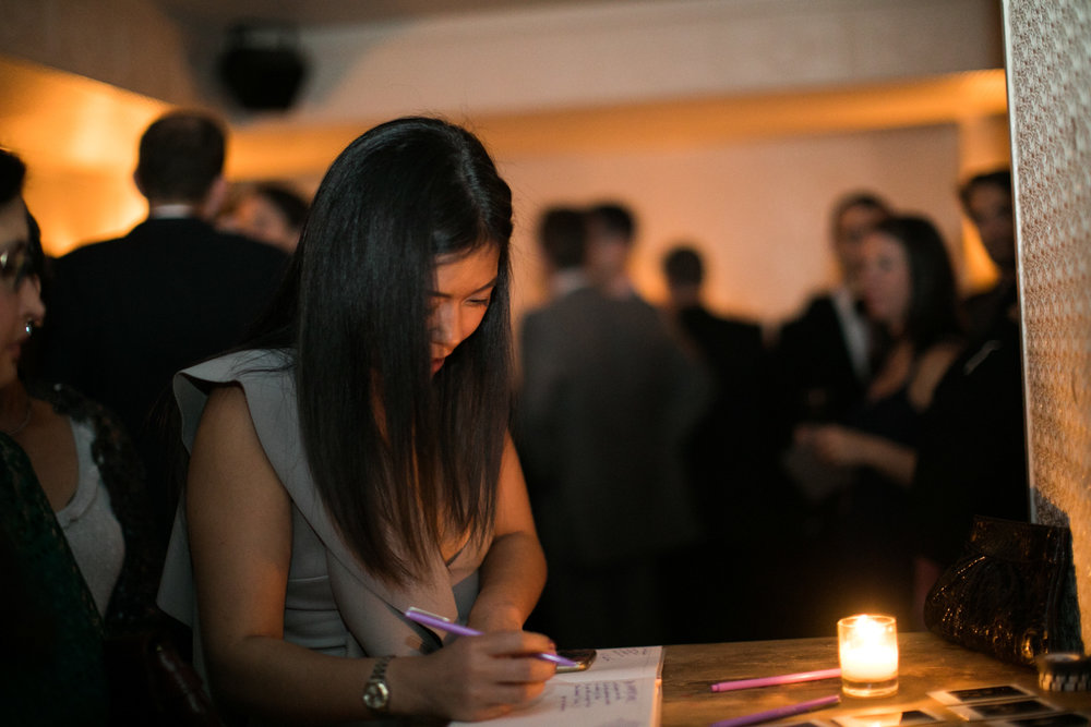 Wedding guest signing a guestbook.