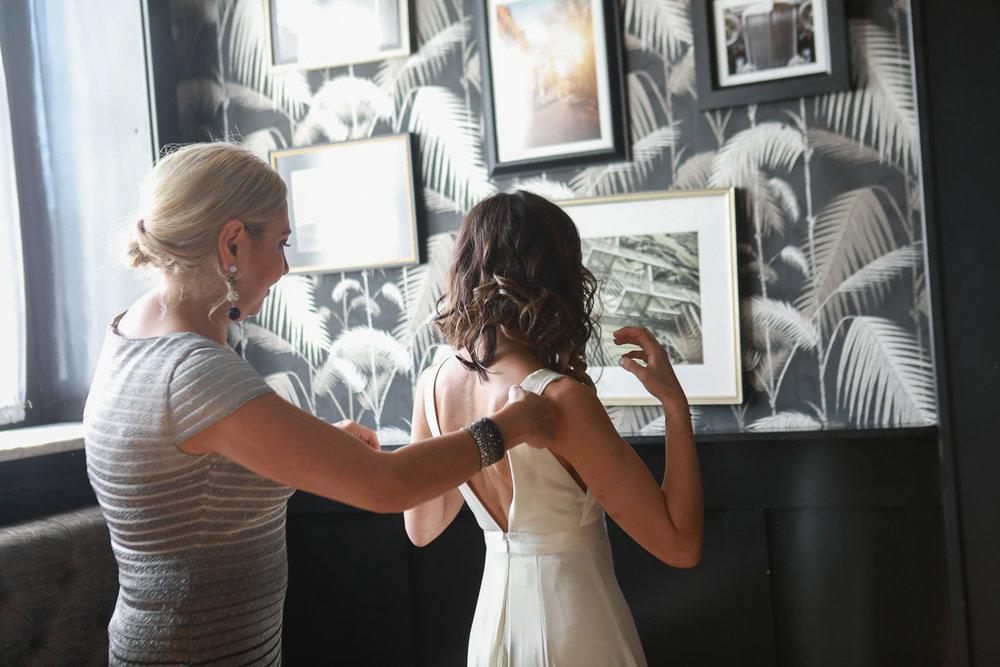 A friend helps the bride into her dress -501 Union Wedding Photos in Brooklyn - Luna & Tom's Wedding