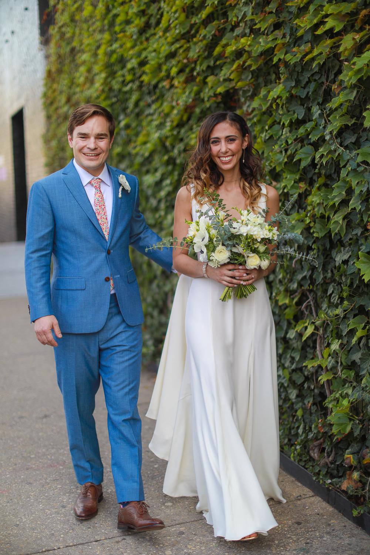 Bride and groom walk against an ivy wall at their wedding -501 Union Wedding Photos in Brooklyn - Luna & Tom's Wedding