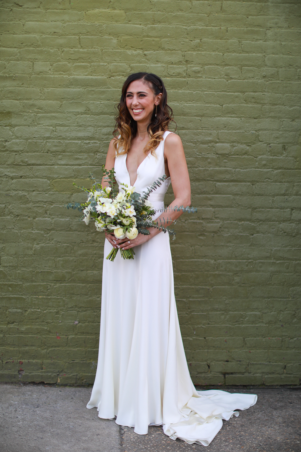 Portrait of a bride in a long wedding gown in front of a green brick mirror - 501 Union Wedding Photos in Brooklyn - Luna & Tom's Wedding
