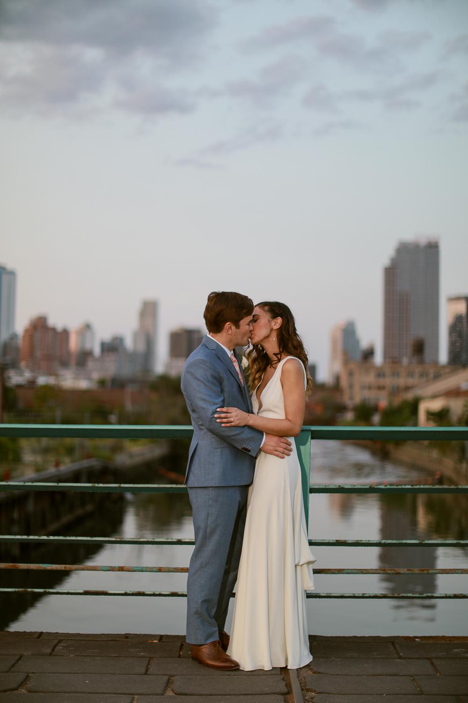 Portrait of a bride and groom kissing against New York skyline - 501 Union Wedding Photos in Brooklyn - Luna & Tom's Wedding