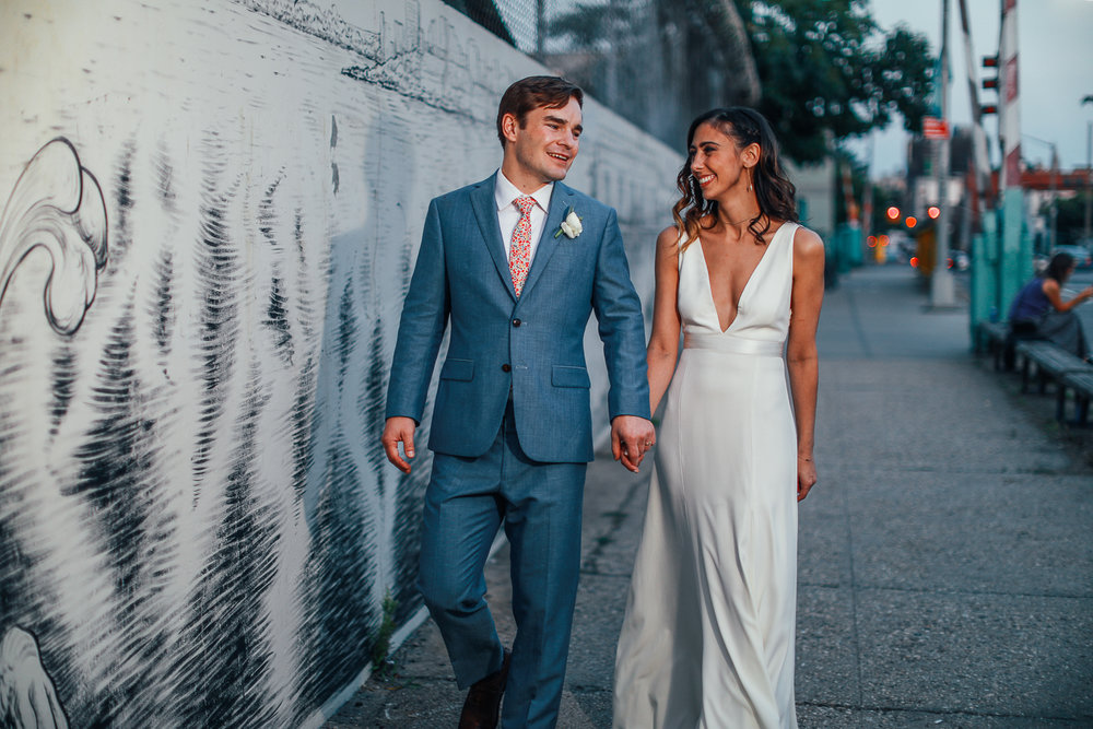 Portrait of a bride and groom holding hands on a New York Street at their Brooklyn wedding - 501 Union Wedding Photos in Brooklyn - Luna & Tom's Wedding
