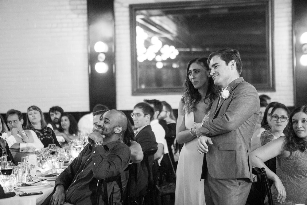 Black and white photo of a couple listening to wedding speeches - 501 Union Wedding Photos in Brooklyn - Luna & Tom's Wedding