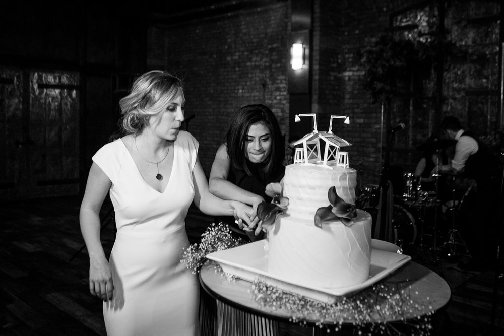 Black and white portrait of brides cutting the cake at their weddingDancing at a wedding reception at 26 Bridge in Brooklyn, New York | 26 Bridge Wedding Photos | Lesbian Brooklyn Wedding | Kristin and Marisa's Wedding
