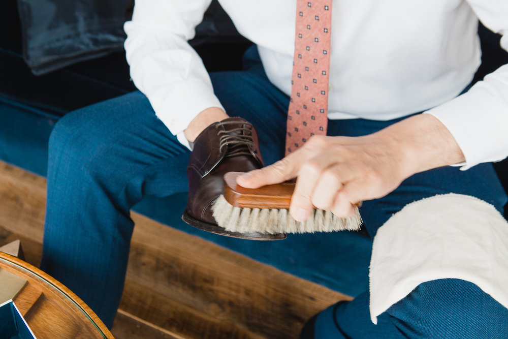 groom is shining his shoe before his wedding